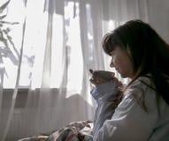 Νέος καφές κατανάλωσης γυναικών καθμένος στο κρεβάτι, ενάντια στο παρ στοκ φωτογραφίες με δικαίωμα ελεύθερης χρήσης