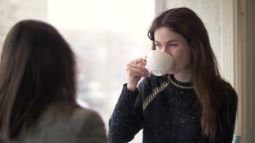 Νέος καφές κατανάλωσης γυναικών και ομιλία με το φίλο κατά τη διάρκεια της συνεδρίασης στον καφέ φιλμ μικρού μήκους