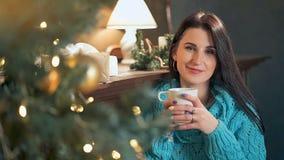 Νέος καφές κατανάλωσης γυναικών μπροστά από το χριστουγεννιάτικο δέντρο στο σπίτι απόθεμα βίντεο
