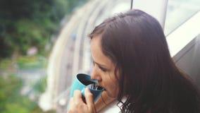 Νέος καφές κατανάλωσης γυναικών brunette όμορφος από το πανοραμικό παράθυρο με την καταπληκτική άποψη πόλεων κίνηση αργή 3840x216 φιλμ μικρού μήκους
