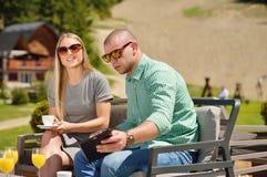 Νέος καφές κατανάλωσης ζευγών στον κήπο τους μια όμορφη θερινή ημέρα Στοκ Εικόνα