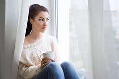 Νέος καφές κατανάλωσης γυναικών και κοίταγμα από το παράθυρο Στοκ φωτογραφία με δικαίωμα ελεύθερης χρήσης