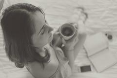 Νέος καφές κατανάλωσης γυναικών στο κρεβάτι Στοκ φωτογραφίες με δικαίωμα ελεύθερης χρήσης