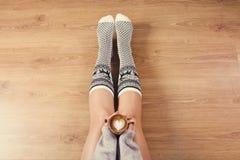 Νέος καφές cappuccino κατανάλωσης γυναικών και κάθισμα στο ξύλινο πάτωμα Κλείστε επάνω των θηλυκών χεριών κρατώντας το φλιτζάνι τ Στοκ φωτογραφία με δικαίωμα ελεύθερης χρήσης