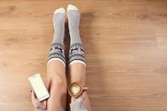 Νέος καφές cappuccino κατανάλωσης γυναικών και κάθισμα στο ξύλινο πάτωμα Κλείστε επάνω των θηλυκών χεριών κρατώντας το φλιτζάνι τ Στοκ Εικόνες
