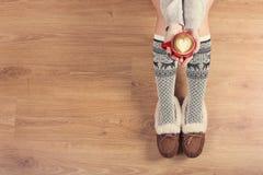 Νέος καφές cappuccino κατανάλωσης γυναικών και κάθισμα στο ξύλινο πάτωμα Κλείστε επάνω των θηλυκών χεριών κρατώντας το φλιτζάνι τ Στοκ Φωτογραφία