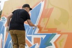Νέος καλλιτέχνης γκράφιτι κατά τη διάρκεια του σχεδιασμού και της ζωγραφικής του έργου τέχνης του Στοκ Φωτογραφία