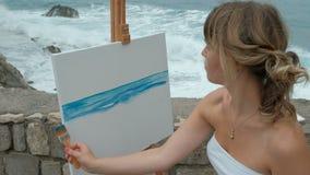 Νέος καλλιτέχνης στην ακτή των ξεχυμένος σαν θάλασσα κυμάτων στο γράψιμο seascape φιλμ μικρού μήκους