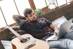 Νέος κιθαρίστας hipster στο σπίτι με την κιθάρα στην κρεβατοκάμαρα που κοιτάζει βιαστικά Διαδίκτυο Στοκ φωτογραφία με δικαίωμα ελεύθερης χρήσης