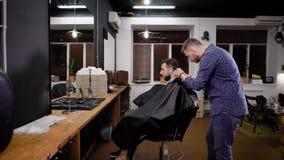 Νέος κουρέας που περπατά γύρω από την πολυθρόνα και που κάνει το κούρεμα με τον κουρευτή ζώων στο barbershop Το γενειοφόρο άτομο  φιλμ μικρού μήκους