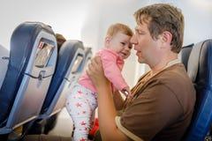 Νέος κουρασμένος πατέρας και η φωνάζοντας κόρη μωρών του κατά τη διάρκεια της πτήσης στο αεροπλάνο που πηγαίνει στις διακοπές Στοκ Εικόνα
