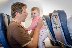 Νέος κουρασμένος πατέρας και η φωνάζοντας κόρη μωρών του κατά τη διάρκεια της πτήσης στο αεροπλάνο που πηγαίνει στις διακοπές Στοκ φωτογραφία με δικαίωμα ελεύθερης χρήσης