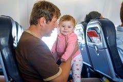 Νέος κουρασμένος πατέρας και η φωνάζοντας κόρη μωρών του κατά τη διάρκεια της πτήσης στο αεροπλάνο που πηγαίνει στις διακοπές Στοκ εικόνες με δικαίωμα ελεύθερης χρήσης