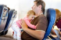 Νέος κουρασμένος πατέρας και η φωνάζοντας κόρη μωρών του κατά τη διάρκεια της πτήσης στο αεροπλάνο που πηγαίνει στις διακοπές Στοκ φωτογραφίες με δικαίωμα ελεύθερης χρήσης