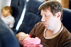 Νέος κουρασμένος πατέρας και ο ύπνος κορών μωρών του κατά τη διάρκεια της πτήσης στο αεροπλάνο που πηγαίνει στις διακοπές Στοκ Εικόνα