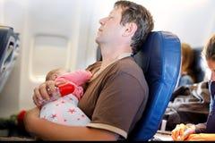 Νέος κουρασμένος πατέρας και ο ύπνος κορών μωρών του κατά τη διάρκεια της πτήσης στο αεροπλάνο που πηγαίνει στις διακοπές Στοκ φωτογραφία με δικαίωμα ελεύθερης χρήσης