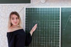 Νέος λεπτός όμορφος ξανθός δάσκαλος σε ένα μαύρο φόρεμα Στοκ Εικόνες