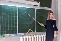 Νέος λεπτός όμορφος ξανθός δάσκαλος σε ένα μαύρο φόρεμα Στοκ εικόνα με δικαίωμα ελεύθερης χρήσης