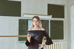 Νέος λεπτός όμορφος ξανθός δάσκαλος σε ένα μαύρο φόρεμα Στοκ εικόνες με δικαίωμα ελεύθερης χρήσης