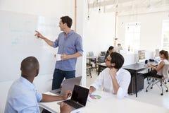 Νέος λευκός που χρησιμοποιεί ένα whiteboard σε μια συνεδρίαση των γραφείων Στοκ Φωτογραφίες