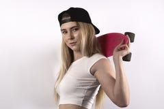Νέος μακρυμάλλης αθλητής γυναικών σπουδαστών με skateboard και ένα β Στοκ Φωτογραφία