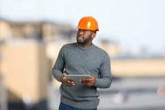 Νέος μαύρος επιστάτης που ελέγχει το αντικείμενο στοκ εικόνες
