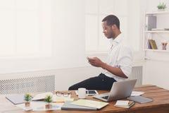 Νέος μαύρος επιχειρηματίας με κινητό στο σύγχρονο άσπρο γραφείο Στοκ εικόνες με δικαίωμα ελεύθερης χρήσης