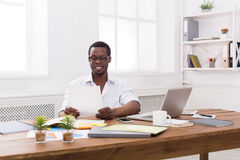 Νέος μαύρος επιχειρηματίας που εργάζεται με τα έγγραφα στο σύγχρονο άσπρο γραφείο Στοκ Φωτογραφίες