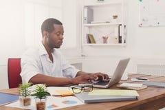 Νέος μαύρος επιχειρηματίας που εργάζεται με το lap-top στο σύγχρονο άσπρο γραφείο Στοκ φωτογραφία με δικαίωμα ελεύθερης χρήσης