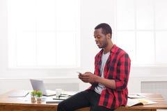 Νέος μαύρος επιχειρηματίας που κάνει ένα τηλεφώνημα σε κινητό στο σύγχρονο άσπρο γραφείο Στοκ Εικόνα