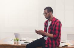 Νέος μαύρος επιχειρηματίας που κάνει ένα τηλεφώνημα σε κινητό σε σύγχρονο Στοκ εικόνα με δικαίωμα ελεύθερης χρήσης