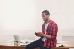 Νέος μαύρος επιχειρηματίας που κάνει ένα τηλεφώνημα σε κινητό στο σύγχρονο άσπρο γραφείο Στοκ εικόνες με δικαίωμα ελεύθερης χρήσης
