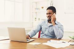Νέος μαύρος επιχειρηματίας που μιλά στο κινητό τηλέφωνο Στοκ Φωτογραφία