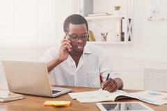 Νέος μαύρος επιχειρηματίας που παίρνει τις σημειώσεις και τη συζήτηση σε κινητό στο σύγχρονο άσπρο γραφείο Στοκ φωτογραφία με δικαίωμα ελεύθερης χρήσης
