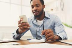Νέος μαύρος επιχειρηματίας που χρησιμοποιεί το κινητό τηλέφωνο Στοκ φωτογραφίες με δικαίωμα ελεύθερης χρήσης