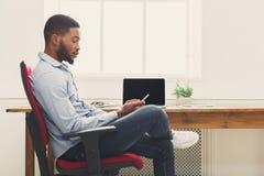 Νέος μαύρος επιχειρηματίας που χρησιμοποιεί το κινητό τηλέφωνο Στοκ εικόνες με δικαίωμα ελεύθερης χρήσης