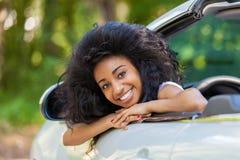 Νέος μαύρος εφηβικός θέση του οδηγού στο νέο μετατρέψιμο αυτοκίνητό της - Α Στοκ Εικόνες