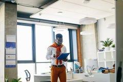 Νέος μαύρος που χρησιμοποιεί τον μπλε φάκελλο Στοκ Εικόνες