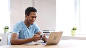 Νέος μαύρος που χρησιμοποιεί Smartphone, on-line που κοιτάζει βιαστικά Στοκ εικόνα με δικαίωμα ελεύθερης χρήσης