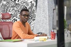 Νέος μαύρος στο γραφείο πίσω από το γραφείο του Στοκ Εικόνες