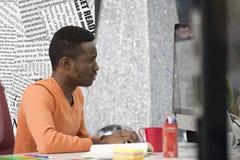 Νέος μαύρος στο γραφείο πίσω από το γραφείο του Στοκ Φωτογραφία