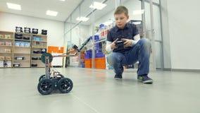 Νέος μηχανικός αγοριών που εξετάζει το μόνος-γίνοντα ρομπότ στο εργαστήριο εφαρμοσμένης μηχανικής απόθεμα βίντεο