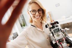 Νέος μηχανικός που παίρνει selfie με τη συσκευή ρομποτικής στο εσωτερικό Στοκ Εικόνες