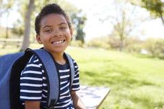 Νέος μικτός μαθητής φυλών με τα χαμόγελα σακιδίων πλάτης στη κάμερα στοκ φωτογραφία