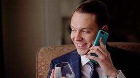 Νέος μοντέρνος νεαρός άνδρας που μιλά στο τηλέφωνο που κρατά ένα ποτήρι του ουίσκυ και που μιλά στο τηλέφωνο που εξετάζει το γυαλ απόθεμα βίντεο