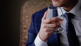 Νέος μοντέρνος τύπος που κρατά ένα ποτήρι του ουίσκυ o cinematic απόθεμα βίντεο