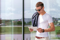 Νέος μοντέρνος φορώντας ένα freelancer που λειτουργεί στην ταμπλέτα Στοκ Φωτογραφίες