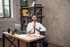 Νέος μοντέρνος όμορφος επιχειρηματίας που εργάζεται στο γραφείο του στο γραφείο που καθορίζει το δεσμό και το χαμόγελό του στοκ φωτογραφία με δικαίωμα ελεύθερης χρήσης