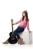 Νέος μουσικός γυναικών με τη συνεδρίαση κιθάρων στον κύβο Στοκ Εικόνες