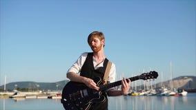 Νέος μουσικός που παίζει σόλο την κιθάρα υπαίθρια φιλμ μικρού μήκους